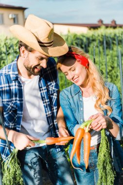 Smiling couple of farmers holding organic carrots in field at farm stock vector
