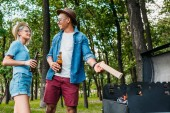 Fotografie multiracial cheerful couple with beer setting fire on grill in summer park
