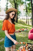 Fotografie side view of smiling young woman in hat and sunglasses taking vegetables from grill in park