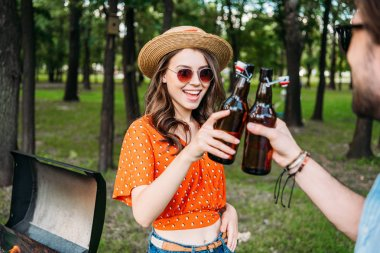 partial view of couple clinking bottles of beer during bbq in park