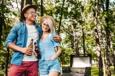 portrait of multiracial couple with beer standing near grill in summer park
