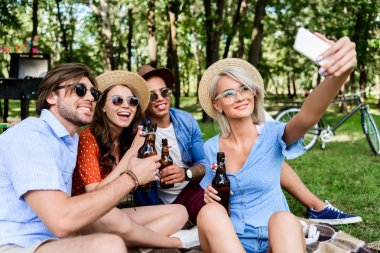Smiling multicultural friends with beer taking selfie on smartphone while resting in summer park stock vector