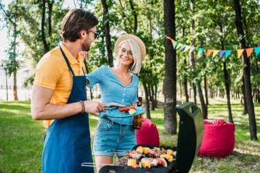 Cheerful couple having barbecue in summer park stock vector