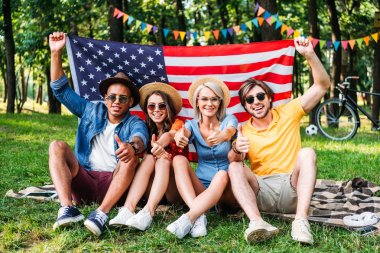 happy multiracial friends with american flag showing thumbs up in summer park