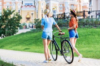 back view of young women in hats with bicycle walking on street