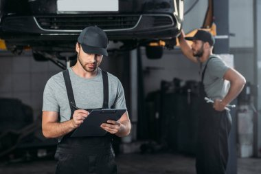 auto mechanic in overalls writing in clipboard, while colleague working in workshop behind