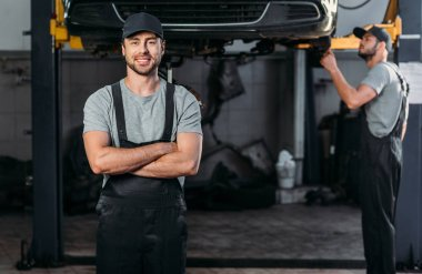 smiling mechanic in overalls posing with crossed arms, while colleague working in workshop behind