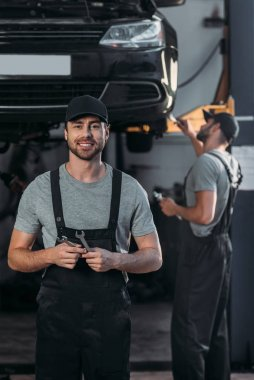 auto mechanic in overalls holding wrenches, while colleague working in workshop behind