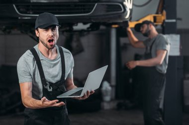 shocked mechanic using laptop, while colleague working in workshop behind