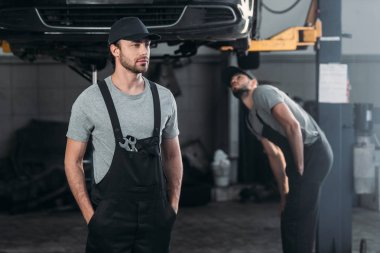 auto mechanic in overalls with colleague working in workshop behind
