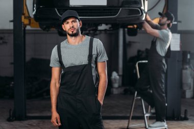 auto mechanic posing in overalls, while colleague working in workshop behind