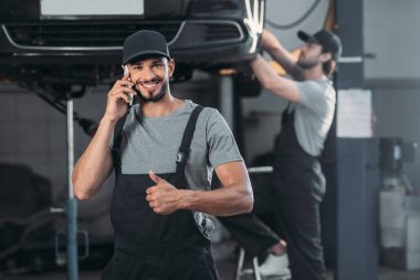 Auto mechanic talking on smartphone and showing thumb up, while colleague working in workshop behind stock vector