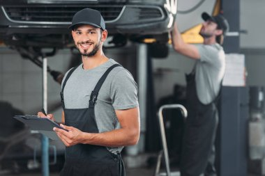 smiling mechanic writing in clipboard, while colleague working in workshop behind