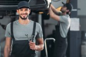 Fotografie s úsměvem Automechanika drží klíče, zatímco kolega pracující v dílně za