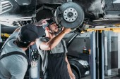 Fotografie automechanici, opravy auto bez kol v dílně