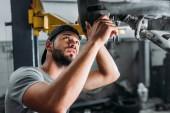 professional technician repairing car in mechanic shop