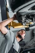 Photo bottom view of workman in uniform repairing car in mechanic shop