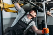 Photo mechanic in uniform working with car in auto repair shop