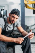Photo professional mechanic holding wrench and sitting in auto repair shop