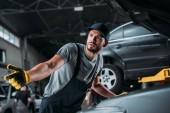 Photo confused manual worker repairing car in mechanic shop