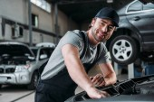 Fotografie smiling auto mechanic working with car in repair shop