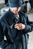 dělník v čepici a držení nástroje v kapse kombinézy
