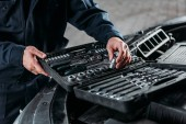 Fotografie partial view of mechanic with tool case in auto repair shop