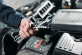 cropped view of mechanic holding wrenches in hand