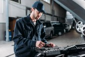 Photo mechanic with tool case in auto repair shop