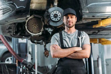 smiling workman posing with crossed arms in auto mechanic shop