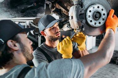 Professional amle mechanics repairing car without wheel in auto repair shop stock vector