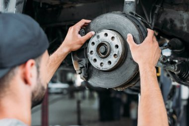 selective focus of mechanic repairing car without wheel in workshop