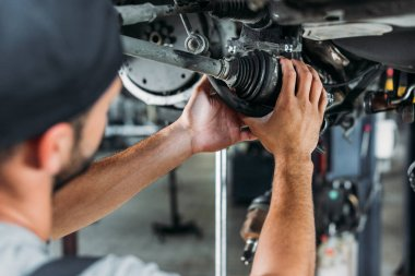 selective focus of professional technician repairing car in workshop
