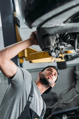 bottom view of workman in uniform repairing car in mechanic shop
