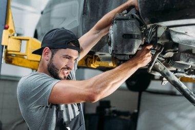Engineer in overalls repairing car in mechanic shop stock vector