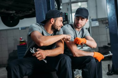 manual workers bumping fists together in mechanic shop