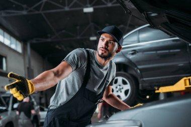 confused manual worker repairing car in mechanic shop