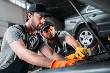 Manual workers repairing car in mechanic shop stock vector