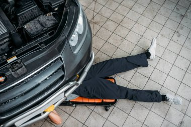 top view of mechanic lying and working under car