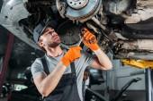 mechanic repairing car without wheel in workshop