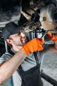 Fotografie profesionální mechanik opravy auto bez kol v dílně