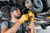 Mechaniker in Uniform reparieren Auto ohne Rad in Werkstatt
