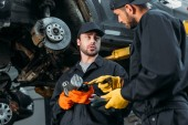 auto mechanics working with car and tools in workshop