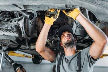 Professional mechanic repairing a car in auto repair shop stock vector