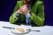 oříznutý snímek člověka v elegantní zelené Sametové sako sedět u stolu s cheburek na desce s modrým pozadím za