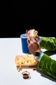 partial view of man in velvet jacket with burger sitting at table with french fries and soda drink on black background