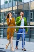Fotografie Paar in Luxus Outfit französischen Hotdogs essen, während des Gehens auf Straße