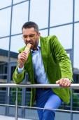 Fotografie portrait of man in green velvet jacket eating french hot dog on street