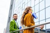 Fotografie Seitenansicht des stilvollen Paar in samt Kleidung mit Soda Getränke und Hot Dogs auf Straße Französisch