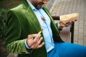 Fotografie Teilansicht der Mann im grünen Samtjacke mit Ketchup auf Hemd und Pommes frites in Händen sitzen auf Bank auf Straße
